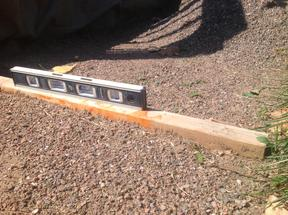 Close-up of buried 2x4 used as leveling guide for crusher fine base for flagstone patio.