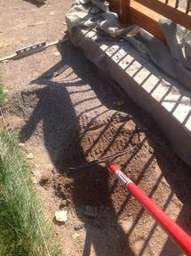 Using a rake to spread crusher fine base for flagstone patio.